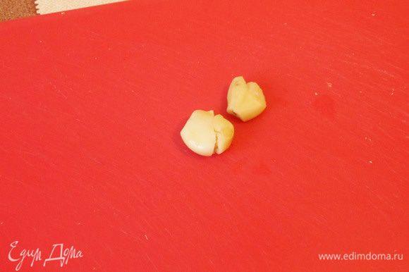Раздавить плоской стороной ножа два зубчика чеснока. Добавить чеснок к гречке.