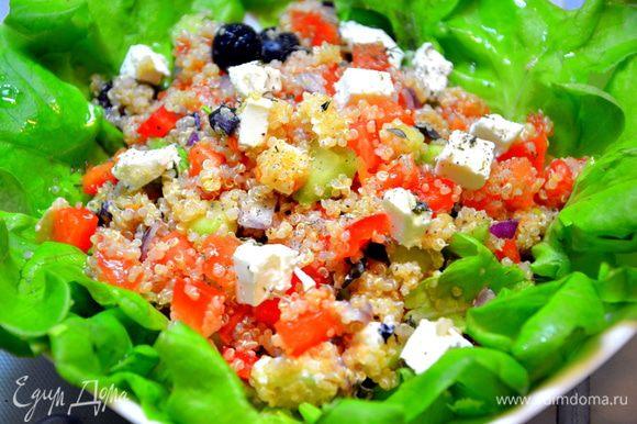 Разложить листья салата на тарелку, выложить сверху греческий салат с киноа, заправить соусом и подавать. Приятного и полезного ужина!