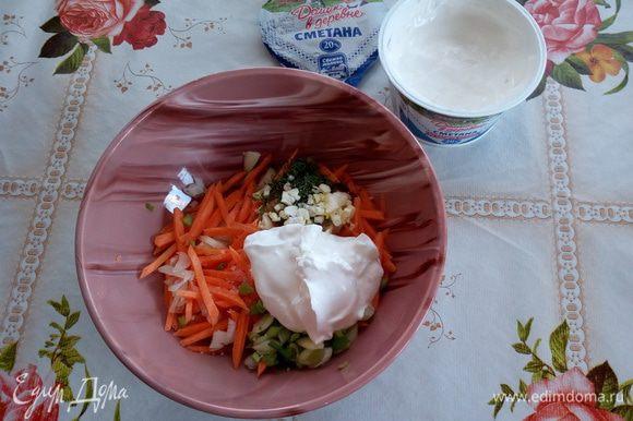 В чашку выкладываем нарезанные овощи, чеснок и зелень. Добавляем 1 ст. л. сметаны. Солим.