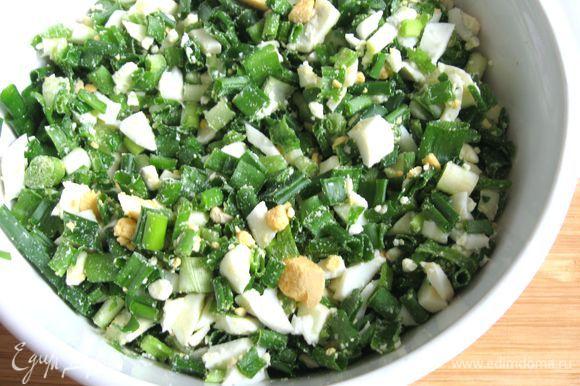 Приготовить начинку из зеленого лука и яиц. Лук помыть, обсушить, мелко порезать, яйца порезать. Объединить, посолить, перемешать.