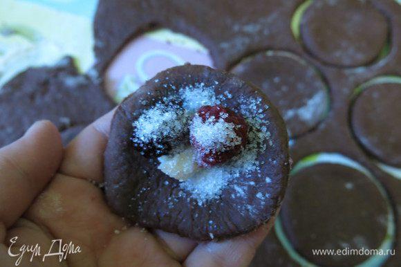 Кладем в центр круга по ягоде, кусочку шоколада, насыпаем сахар. На один вареник — 1/4 чайной ложки сахара.