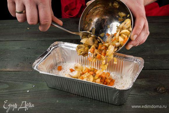 Форму смазать маслом, высыпаем отварной рис, дальше — жареные грибы с овощами.
