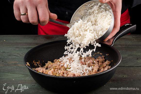 Лук мелко нарезать, обжарить до золотистого цвета на растительном масле, добавить рис, тунца и потушить 2 минуты.