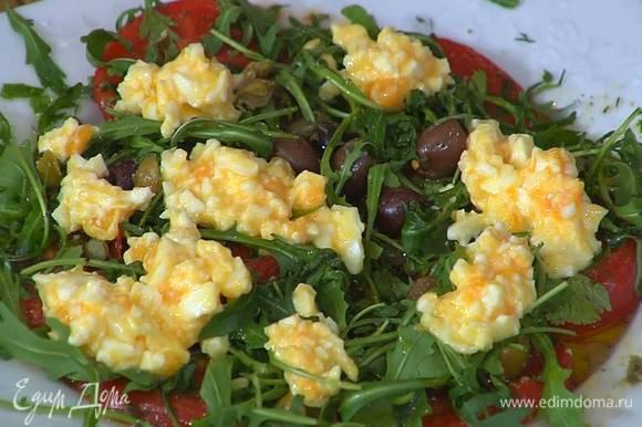 Отваренные яйца почистить, размять вилкой и выложить на помидоры с руколой.