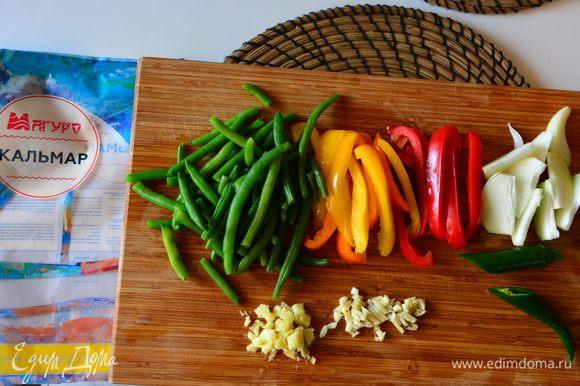 Приготовить овощи: лук нарезать вдоль, перец полосками, фасоль разморозить, чеснок и имбирь мелко нарезать, зеленый перец чили разделить пополам.