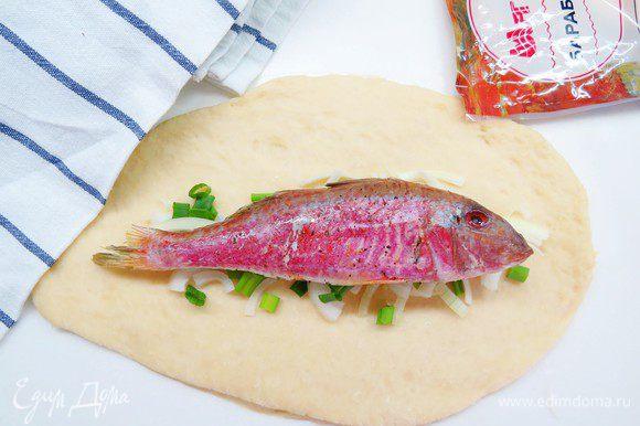 Тесто раскатываем в довольно тонкий пласт, на тесто выкладываем лук и часть зеленого лука. Сверху кладем нашу рыбку.