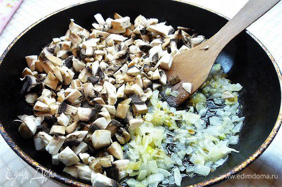 Лук мелко нарезаем и обжариваем на оливковом масле до золотистого цвета, добавляем нарезанные мелким кубиком шампиньоны.