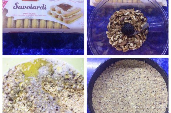 Начинаем с основы чизкейка. Крошим печенье при помощи блендера (у меня дома оказалось только печенье савоярди). Измельчаем орехи. Растапливаем сливочное масло. Соединяем крошку печенья, орехи, масло и все тщательно смешиваем. У меня еще оставался бисквит шоколадный от какого-то десерта, совсем мало, я и его добавила (граммов 50 было). Дно формы застелить пекарской бумагой и распределить крошку по всей форме, плотно приминая. Отправляем в морозилку минут на 20.