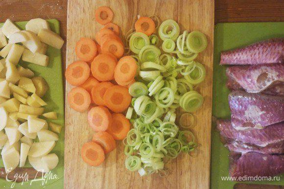 Нарезать овощи тонкими кружками и кубиками. У рыбы отрезать плавники и головы, залить их холодной водой.