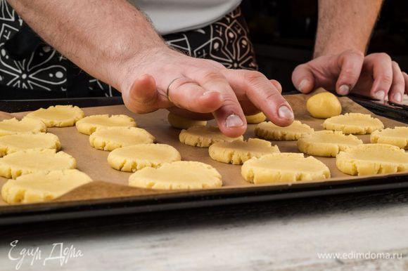 Шарики ладонью раздавить так, чтобы получились печенья. После чего поместить противень на 10 минут в разогретую духовку.