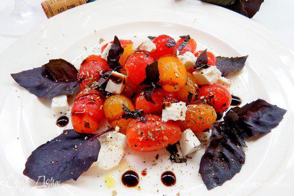 В емкости для салата приправить помидоры сухими итальянскими травами (состав выбирайте на свой вкус), черным перцем, уксусом, оливковым маслом, базиликом, добавить кубики феты. Дать охладиться и настояться в холодильнике не менее 30 минут. При необходимости перед подачей приправить солью.
