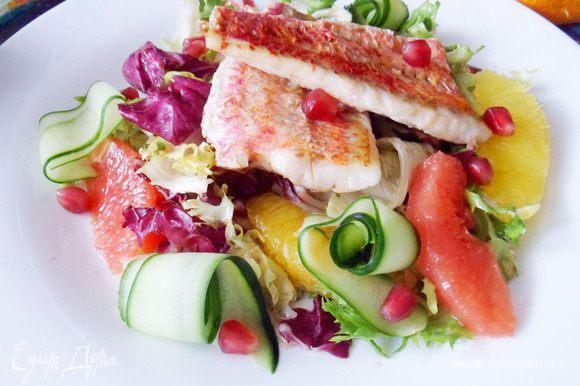 Сервируем блюдо. Выкладываем салат, теплое филе барабульки. Огурец нарежем тонкими лентами при помощи ножа для чистки овощей. Украшаем салат ленточками огурца и зернами граната. Очень вкусно и красиво! Приятного аппетита!