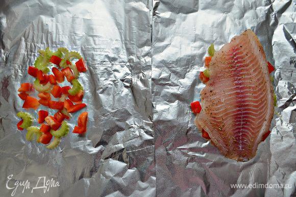 Двойной слой фольги (прямоугольник примерно 30Х40 см) немного смажьте растительным маслом. Выложите порезанный перец с сельдереем, затем филе рыбы и сбрызните слегка лимонным соком.