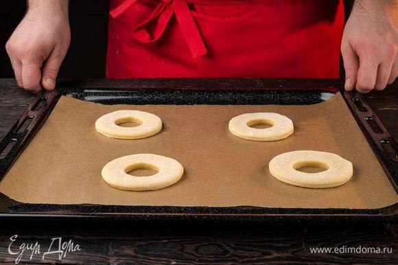 Раскатайте тесто в пласт толщиной около 1 см. Вырежьте стаканом или бокалом кружки, а рюмкой внутри маленькие кружки. Выложите пончики на противень для расстойки.