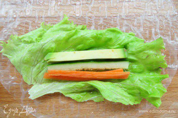 Один рисовый блинчик кладем на разделочную доску, наливаем на него 2 столовые ложки воды, распределяем воду руками по всему блинчику, он смягчится. В центр кладем лист салата, на него — полоски моркови, огурца и авокадо в произвольном порядке.