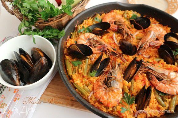 За 1-2 минуты до полной готовности риса с овощами поместить в сковороду морепродукты: креветки, щупальца кальмара, мидии, накрыть крышкой. Выключить огонь, перед подачей дать постоять минут 5. Украсить зеленью петрушки.