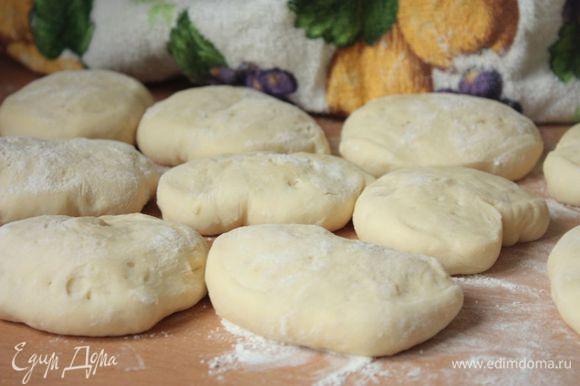 Разложите заготовки для булочек на припыленную мукой рабочую поверхность, накройте полотенцем и оставьте их расстаиваться на полчаса.
