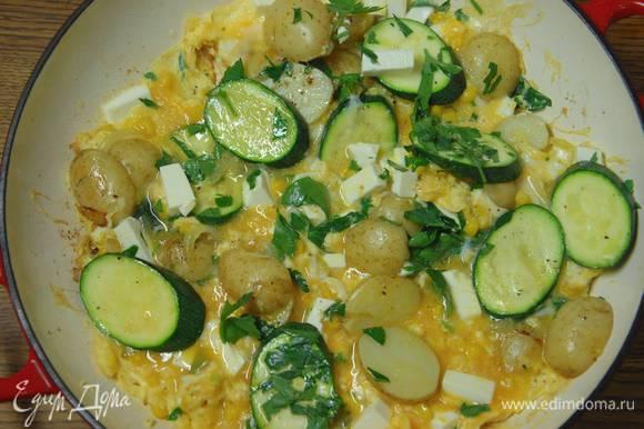 Яичную массу вылить в сковороду с обжаренными овощами, сверху разложить фету, посыпать петрушкой и готовить тортилью до той степени прожарки, которая вам по вкусу.