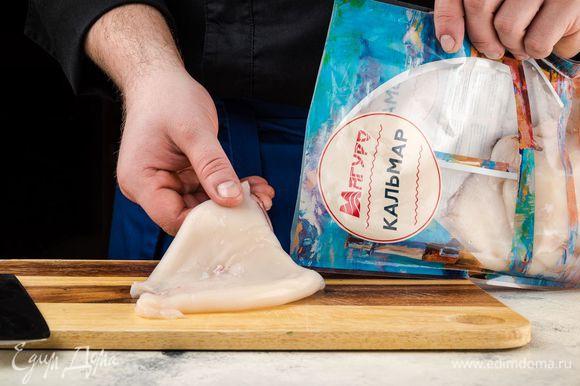 Кальмары ТМ «Магуро» почистите, вымойте и просушите бумажным полотенцем. Очень острым ножом сделайте на тушке каждого кальмара надрезы вдоль и поперек, чтобы получились клеточки.