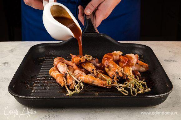 Готовые креветки еще на горячей сковороде смажьте соусом барбекю. И снова верните на огонь на 2 минуты.