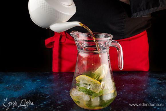 Вторую часть лимона порежьте тонкими ломтиками. Добавьте в кувшин мед, мяту и лед и залейте чаем.