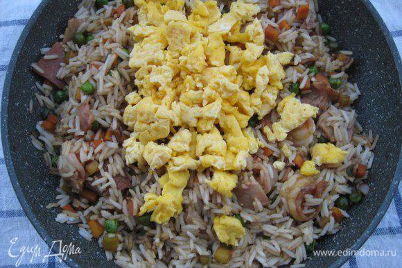 Добавить отварной рис и кусочки омлета, перемешать, дать рису прогреться. Снять с огня.