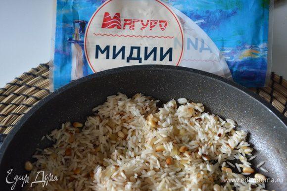 С риса слить воду, добавить рис к луку и орешкам, жарить еще 2-3 минуты.