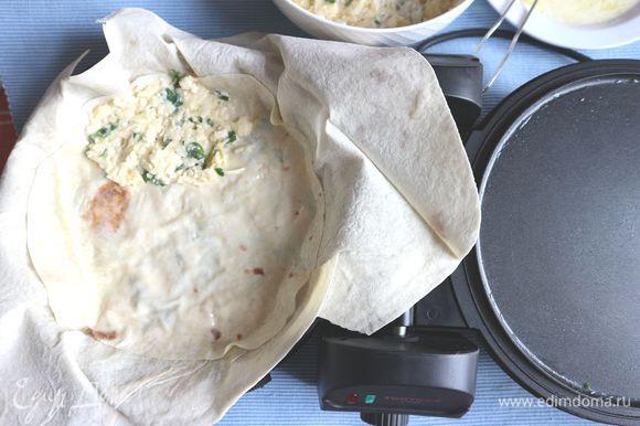 Сверху положить лист лаваша, вырезанный ножницами в форме круга. Затем, смазать масляно-йогуртовой смесью. Снова — начинка. И так продолжать, пока не используется вся начинка.