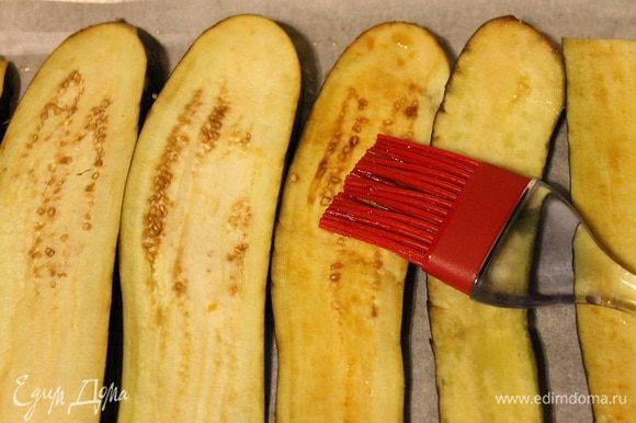 Баклажаны понадобятся большие и длинные, нарезать их пластинами 3–5 мм, смазать с двух сторон маслом и соевым соусом, выложить на противень, застеленный пергаментом. Запекать при температуре 180°C 10–15 минут. Остудить.
