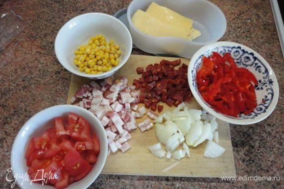 Колбасу (я взяла чоризо и уже не добавляла перца, хватило ее остроты), бекон и лук нарезать кубиками. Перец — полосками. Помидор предварительно очистить от кожицы с помощью кипятка и холодной воды и нарезать также кубиками. Сыр нарезать слайсами.