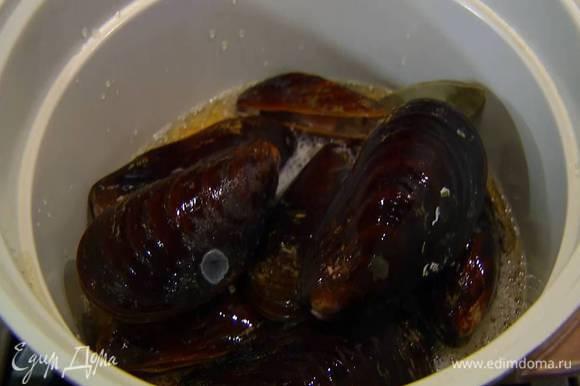 Разогреть тяжелый сотейник, поместить в него мидии и лавровый лист, влить сидр, накрыть крышкой и прогревать 7‒8 минут, пока раковины не откроются.