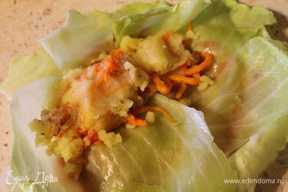 Сверху накрыть еще одним листом капусты и ближе к краю положить начинку из картофеля и овощей.