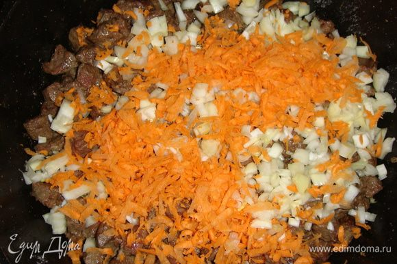 Лук нарезать кубиками, морковь натереть на крупной терке и добавить к печени. Посолить, поперчить, добавить сливочное масло, все перемешать и тушить под закрытой крышкой 7 минут.