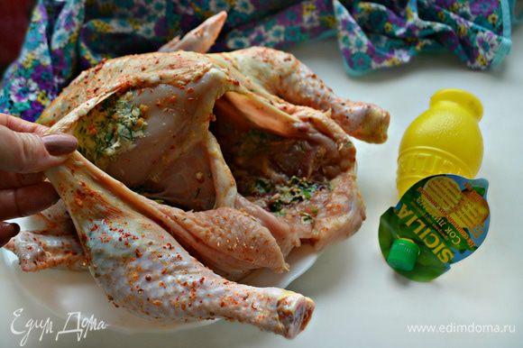 Кожу со стороны ночек у курицы подденьте и оттяните. Положите внутрь масляную смесь и равномерно распределите по ножкам и грудке. Внутри курицу также немного смажьте масляной смесью.