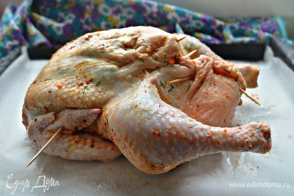 Отверстие курицы зашейте или скрепите зубочистками, крылья подверните внутрь и закрепите зубочистками, чтобы не обгорали. Выложите тушку на противень грудкой вверх и запекайте при 180°С 1-1,15 ч. Если курочка быстро подрумянивается, прикройте ее фольгой.