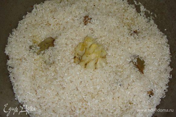 Чеснок вынуть, положить вымытый лавровый лист. Выложить в казан рис, в середину вдавить чеснок.