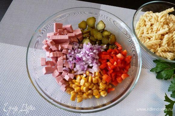Колбасу и сладкий перец режем кубиком, маленькие маринованные огурчики (пикули) колечками. Если лук острый, то его стоит залить горячей водой на полминутки, чтобы ушла горечь. А если лук сладкий, то его просто мелко нарезать. Добавить консервированной кукурузы.
