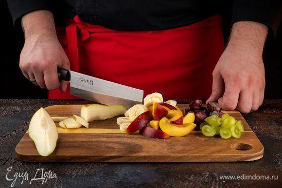 Нарежьте фрукты небольшими кусочками. Ягоды винограда разрежьте пополам и удалите косточки.
