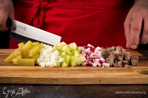Мясо, картофель, яйца отварите. Также можно заменить мясо сосисками, колбасой или сардельками. Нарежьте кубиками мясо, свежие очищенные огурцы, картофель. Редис нарежьте тонкими ломтиками, яичные белки — кубиками.