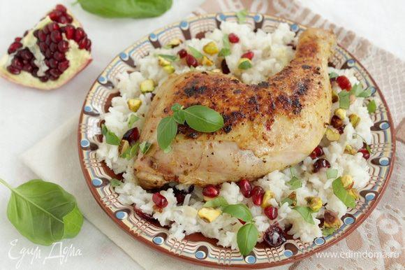 Переложите рис на тарелку, сверху выложите курицу, посыпьте рублеными фисташками, зернами граната и зеленью.