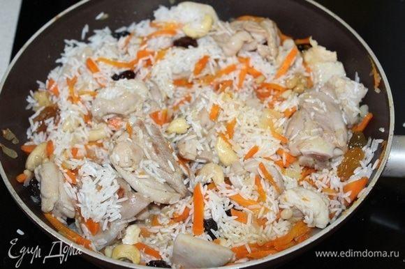 Затем добавляем рис, перемешиваем. В отдельной сухой сковороде слегка прокалить орешки и добавить к рису. Сюда же добавляем изюм.