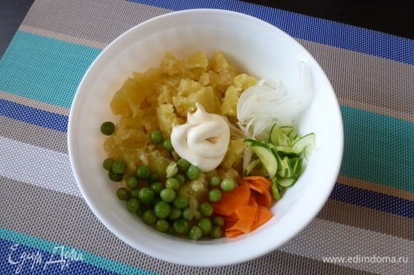 Соединим в салатнике мятый картофель, лук, огурец, морковь и зеленый горошек. Заправим майонезом.