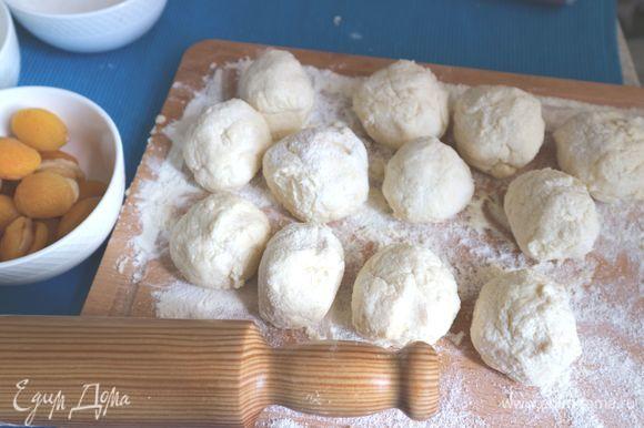 Разделить тесто на 12 кусочков, скатать в шарики на поверхности, хорошо присыпанной мукой (можно добавить на поверхность еще немного манной крупы).