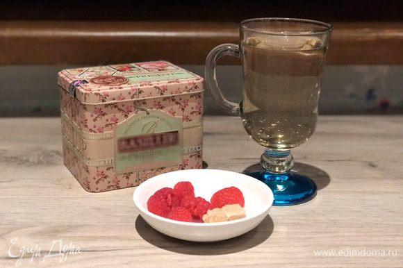 Когда чай заварился, вытаскиваем ложечку (мне понадобилось на это 3 минуты). Прямо в чашку закладываем малину и тростниковый сахар.