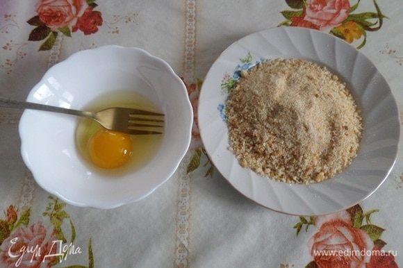 В чашечку разбиваем яйцо и слегка взбиваем с помощью вилки. В тарелку высыпаем панировочные сухари.