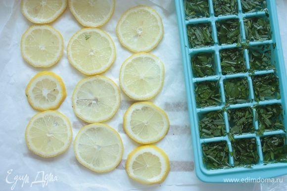 В формочки для льда выложите сначала отложенную треть зелени, которую вы крупно порвали, а затем залейте настоем. Один лимон нарежьте на тонкие-тонкие дольки. Отправьте все охлаждаться в морозилку.