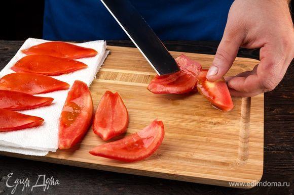 Приготовьте ароматные вяленые помидоры для закуски. Помидоры промойте, вырежьте плодоножку, разрежьте пополам и вычистите ложкой семена вместе с соком. Выложите на бумажные полотенца, чтобы убрать сок.
