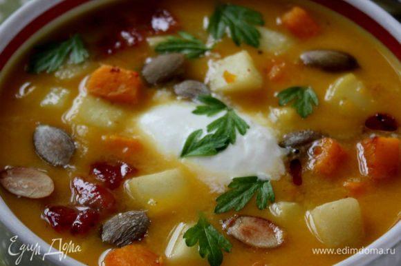 Суп разлить по суповым чашкам или тарелкам. В каждую положить смесь из тыквы и яблок, ломтики бекона и сметану. Сверху посыпать семенами тыквы и петрушкой, влить тыквенное масло. Приятного аппетита!
