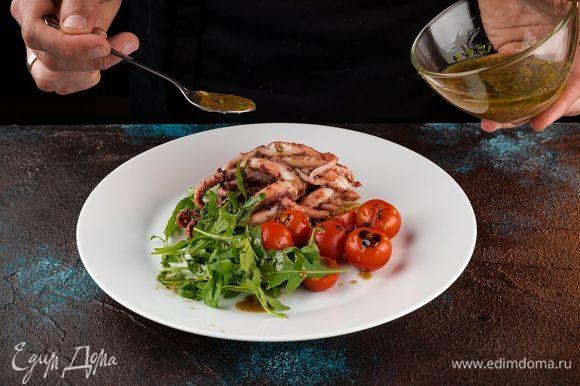 Выложите на широкую тарелку руколу, щупальца кальмара и помидоры черри. Полейте все заправкой.