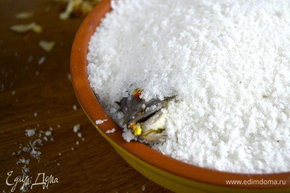 Взбить белки с водой, залить ими соль, тщательно вымешать до липкого состояния. Дно формы для запекания выложить раствором для соли. Положить на него рыбу, укутать одеялом из соли. Поставить форму в духовку на 30 минут.